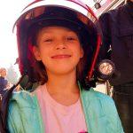 Uczennica szkoły podstawowej w kasku strażackim