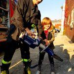 Uczennica SP z narzędziem strażaków