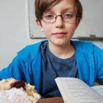 Uczeń zajada się pączkiem na zajęciach