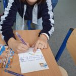 Uczennica wypisuje pocztówkę