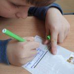 Uczeń klasy drugiej pisze pocztówkę
